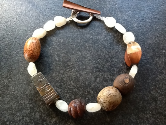 """The necklace is named """"DIALOGUE"""" and is 21.5"""" long.  The widest bead is 1.25"""" and the toggle is 2.75"""" long.  I recommend chunky silver earrings with this necklace. It is very chunky, but not very heavy due to the lightness of wood beads.  It is $139 which includes shipping and insurance."""