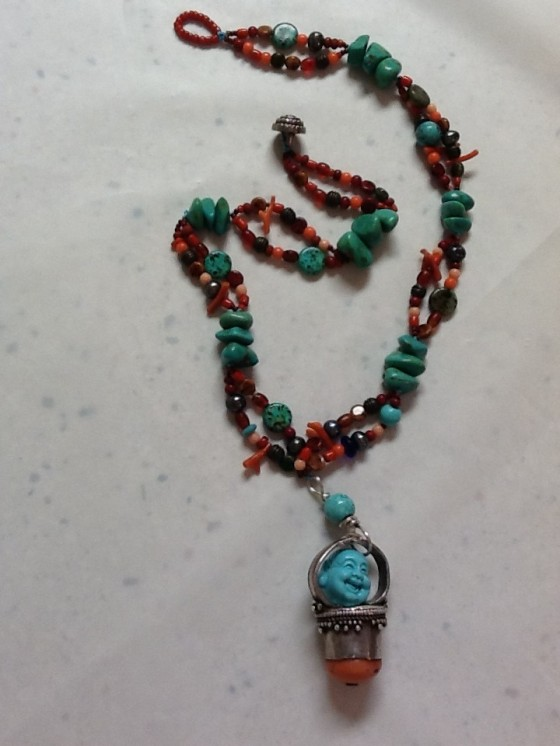 "The two strand ""Treasure"" necklace is strung with heavy turquoise thread and ""woven"" through three turquoise beads every few inches.  It ends with a coral clasp around a vintage button. It measures 21"" and the centerpiece is 3"" long.  It is priced at $155 which includes shipping and insurance."