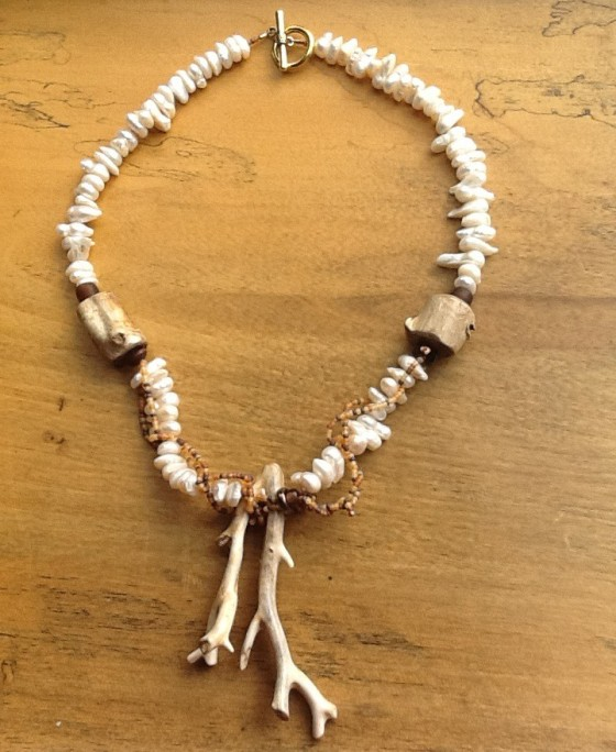 "I have paired the petrified bleached wood from Alaska with large baroque pearls (read interesting and organic shapes), and beige multi-toned glass seed beads woven in and out of the wood. The necklace is just shy of 21"".  It has a pewter-based gold-coated clasp and can be worn casually or dress-up.  Just remember, it is no longer precious; it is now a statement piece! The price is $175 which includes shipping and insurance."